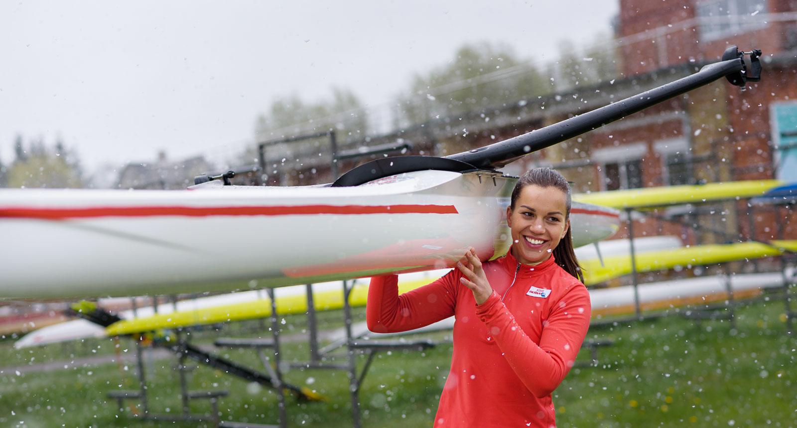Milda Valčiukaitė neša valtį ActiveLife reklamos filmavime. Lauke sninga