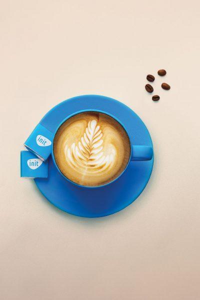 Mėlynas kavos puodelis su INIT šokoladukais ant švaraus fono